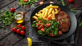 Grilled sirloin steak with potato fries and vegetables, tomato salad in a black plate. rustic table.  royalty free stock photography