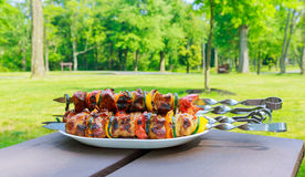 Grilled skewers on the plate made with pork chicken, bacon and vegetables. Stock Photo