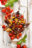 Grilled skewers of vegetables and meat in a herb marinade on white plate Royalty Free Stock Photos