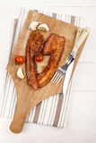 Grilled slice pork bacon with garlic and tomato on a wooden boar Stock Photography