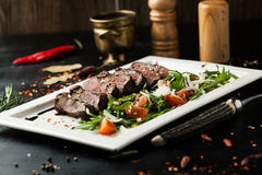 Grilled sliced beef steak with salad on a plate Royalty Free Stock Photo