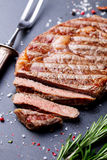Grilled sliced beef steak on slate stone table. Top view. royalty free stock image