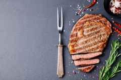 Grilled sliced beef steak on slate stone table. Top view. Copy space royalty free stock photos