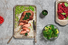 Grilled sliced meat with green sauce on the stone surface Royalty Free Stock Photography