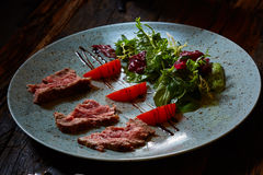 Grilled sliced roast beef and green salad. And tomatoes stock photo