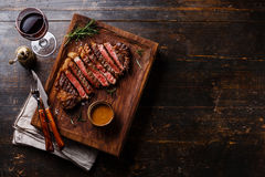 Grilled sliced Steak Rib eye with Pepper sauce. And Red wine on wooden background copy space royalty free stock images