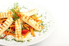 Grilled slices of homemade halloumi cheese with salad, fresh herbs and organic tomatoes. Fried halloumi cheese with grill. Grilled slices of homemade halloumi royalty free stock image