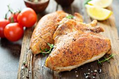 Grilled or smoked chicken breast with bone and skin. On a cutting board stock image
