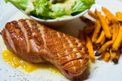 Grilled smoked duck with yellow Mango sauce eat with green salad and sweet potato fried Stock Photo