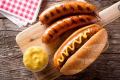 Grilled Smoked Sausages. Delicious grilled smoked sausages on a roll with yellow mustard royalty free stock photography