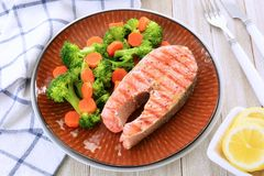 Grilled sockeye salmon steak horizontal. Grilled sockeye salmon steak with steamed broccoli and carrots and lemon slices.  In horizontal format and shot in Stock Photo
