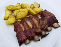 Grilled spare pork ribs barbecue and roasted potatoes royalty free stock photography