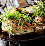 Grilled spicy chicken legs with herbs. And spices on a black plate Royalty Free Stock Photo