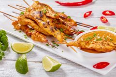Chicken satay with tasty peanut sauce. Grilled spicy Chicken satay on skewers on a white rectangular plate with peanut sauce. red chili peppers, lime slices and stock photos