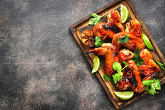 Grilled spicy chicken wings.Top view with copy space. Grilled spicy chicken wings on a wooden cutting board on dark slate,stone or metal background.Top view Stock Photo