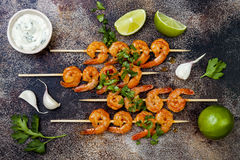 Grilled spicy lime shrimp skewers with creamy avocado garlic cilantro sauce. Top view, overhead, flat lay. Royalty Free Stock Image