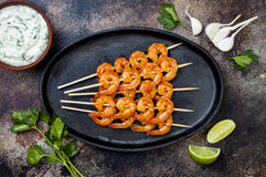 Grilled spicy lime shrimp skewers with creamy avocado garlic cilantro sauce. Top view, overhead, flat lay, copy space. Grilled spicy lime shrimp skewers with royalty free stock images