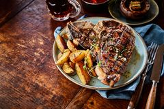 Grilled spicy T-bone steak with potato wedges stock photos