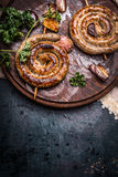 Grilled spiral sausages with garlic and seasoning on dark wooden background, top view Stock Photos