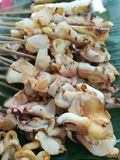 Grilled squid. Fresh Squid on skewers is being grilled by a street vendor in the most famous flea market stock photos
