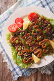 Grilled squid rings on skewers and vegetables close-up. vertical Stock Photos