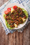 Grilled squid on skewers with vegetables close-up. vertical top Stock Photo