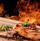 Grilled steak. Grilled beef steak with flames on background royalty free stock image