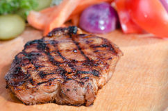 Grilled steak. Steak on wooden plate, in background marinated vegetables royalty free stock image