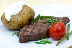 Grilled steak with baked potato and cream Stock Photo