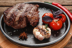 Grilled steak on black plate. American junk food. Delicious beef steak served with grilled tomatoes and garlic and decorated with basil and chili, close up view Stock Photography