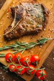 Grilled steak on the bone and tomatoes on a branch Royalty Free Stock Photography