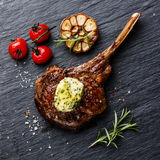 Grilled Steak on bone Veal rib with herb butter. On stone slate background Royalty Free Stock Images