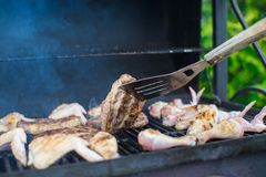 Grilled steak and chiken cooking on an open barbecue Stock Photos