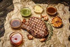 Grilled steak with different sauces, on parchment. vertical top view Royalty Free Stock Image