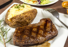 Grilled steak dinner. Grilled sirloin steak dinner with baked potato stock photography