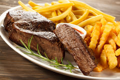 Grilled steak, French fries and beans Stock Image