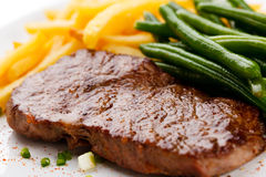 Grilled steak, French fries and green bean Stock Photos