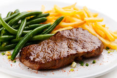 Grilled steak, French fries and green beans Royalty Free Stock Images