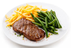 Grilled steak, French fries and green beans Stock Image