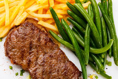 Grilled steak, French fries and green beans Royalty Free Stock Image