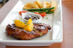 Grilled steak with french fries and vegetables on table Royalty Free Stock Photos