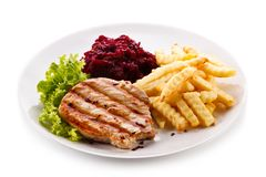 Grilled steak, French fries and vegetables on white background stock images