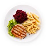 Grilled steak, French fries and vegetables on white background stock photos
