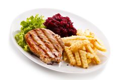 Grilled steak, French fries and vegetables on white background stock photography