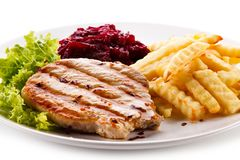 Grilled steak, French fries and vegetables on white background stock image