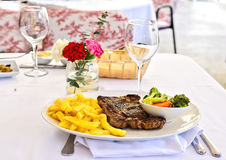 Grilled steak with french fries and vegetables on a white table outdoors. Fresh served Stock Photo