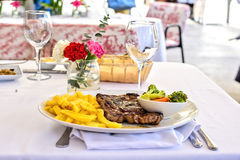 Grilled steak with french fries and vegetables on a white table outdoors. Fresh served Royalty Free Stock Images