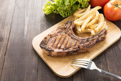 Grilled steak with french fries on a wooden board. Royalty Free Stock Photo