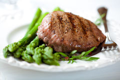 Grilled steak on green asparagus Royalty Free Stock Photo
