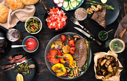 Grilled steak with grilled vegetables, beer and wine. On a dark wooden table, top view. Dinner table concept Royalty Free Stock Photo